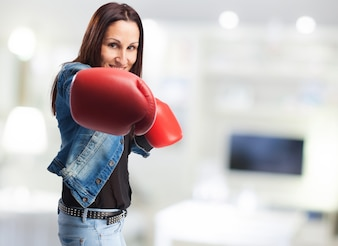 Mujer sonriente en chaqueta vaquera con guantes de boxeo dando un puñetazo