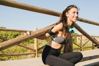 Mujer sonriente estirando en valla