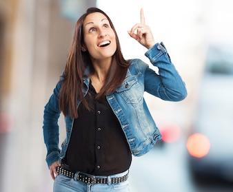 Mujer sonriente señalando hacia arriba