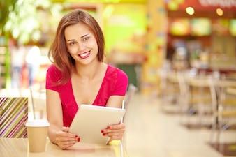 Mujer sonriente sosteniendo una tableta