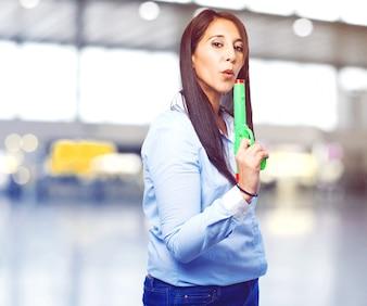 Mujer soplando la punta de una pistola verde de juguete