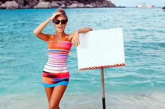 Mujer sorprendida con cartel en blanco en la playa