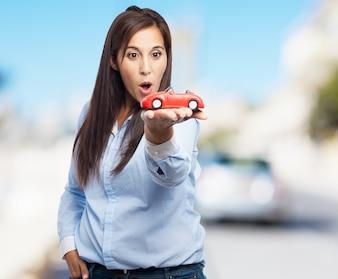 Mujer sosteniendo un coche de juguete de color rojo con fondo borroso