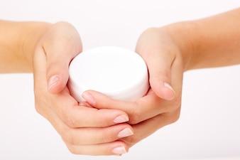 Mujer sosteniendo un envase de crema