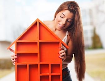 Mujer sujetando una casa de color naranja