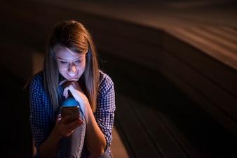 Mujer texting. Closeup joven feliz sonriente hermosa mujer alegre mirando la lectura de teléfono móvil de la célula que envía los sms parque aislado fondo urbano del paisaje urbano. Expresión de la cara positiva emoción humana