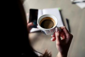 Mujer tomando una taza de café mientras mira su teléfono inteligente