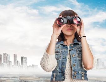 Mujer usando unos prismáticos con la ciudad de fondo