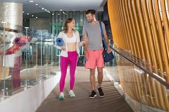 Mujer y hombre charlando en la puerta del gimnasio