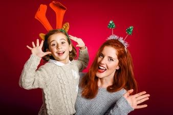 Mujer y niña pequeña con adornos de navidad en sus cabezas