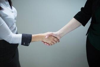 Mujeres anónimas dándose la mano en gris