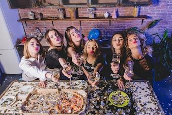Mujeres con champán enviando aire beso
