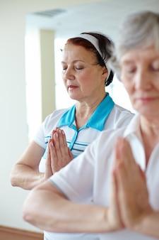 Mujeres mayores haciendo posturas de yoga relajantes