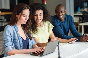 Multiétnico grupo de jóvenes que estudian con ordenador portátil