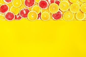 Naranjas y naranjas sanguinas sobre una superficie amarilla