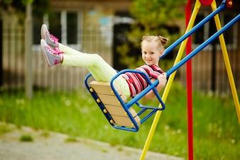 Niña jugando sola en el parque infantil