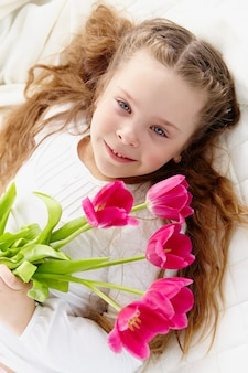 Niña alegre sosteniendo flores