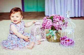 Niña bonita en vestido con flores se sienta ante la linterna de color rosa y ramo de lilas