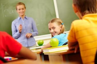 Niña con camiseta azul sonriendo en clase