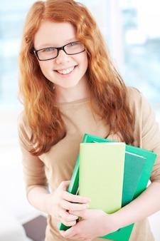 Niña con gafas y libros en el colegio