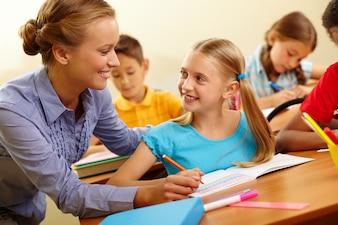 Niña dibujando con la maestra ayudando en clase