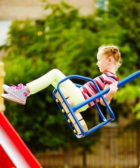 Niña feliz columpiandose en el parque infantil