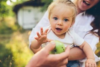 Niña feliz mirando como le ofrecen una manzana