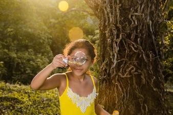 Niña haciendo burbuja de jabón a lado de árbol