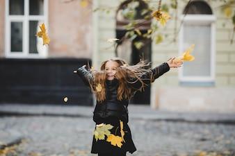 Niña lanzando hojas por los aires