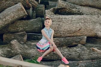Niña moderna sentada en un tronco
