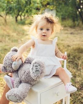 Niña pequeña con un vestido y un oso de peluche