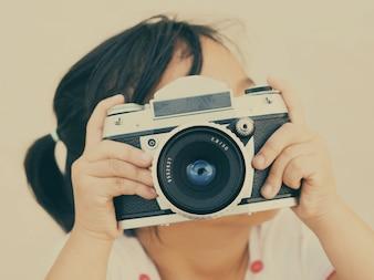 Niña pequeña con una cámara de fotos antigua