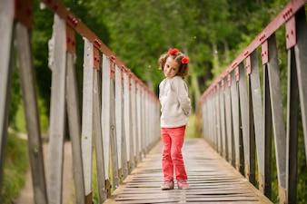 Niña pequeña encantadora cruzando un puente