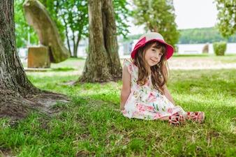 Niña pequeña sentada en el césped con un sombrero