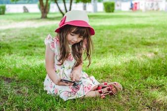 Niña pequeña sentada en el césped mirando un móvil con auriculares