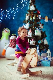 Niña pequeña sonriente al lado del árbol de navidad