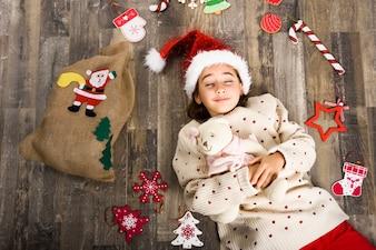 Niña pequeña vestida de papa noel tumbada boca arriba rodeada de adornos navideños y un saco
