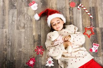 Niña pequeña vestida de papa noel tumbada boca arriba rodeada de adornos navideños