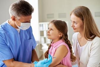Niña recibiendo vacuna en la consulta del médico