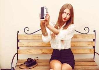 Niña sentada en un banco de madera haciéndose una foto