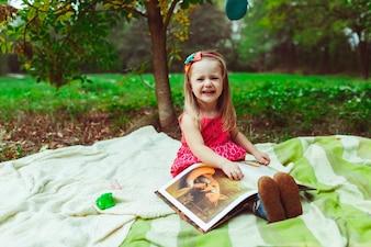 Niña sonriendo con un libro de dibujos