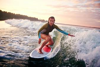 Niña surfeando al atardecer