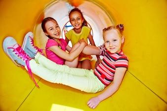 Niñas jugando en el tobogán en el parque infantil
