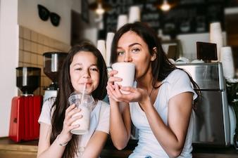 Niñas sentadas en la cafetería bebiendo