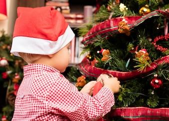 Niño adornando el árbol de navidad