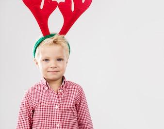 Niño con cuernos de reno rojos