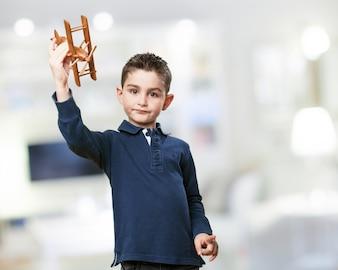 Niño con un avión de madera