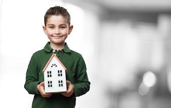 Niño con una casa en sus manos