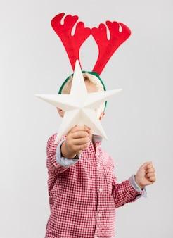 Niño con una estrella del árbol y cuernos de reno