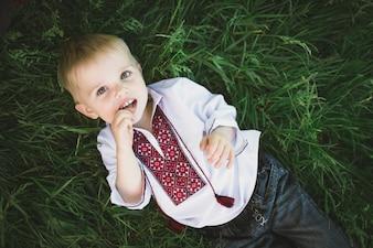 Niño con una mano en la boca tumbado en el suelo